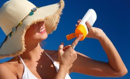 woman-with-hat-applying-sunscreen